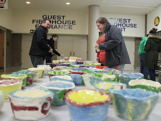 Attendees of Empty Bowls browse the selection of bowls.