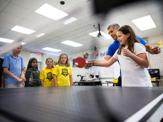 Naples Philharmonic harpist Dickie Fleisher, also a champion pingpong player, teaches Falyn Boening, 10, how to play table tennis during a special combined music and PE session at Tommie Barfield Elementary School in Marco Island on Friday, Nov. 17, 2017.