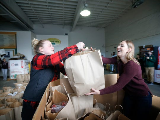 Volunteers Marissa Petrie (left) and Sara Linz sort out bags of food to be given out at the Freestore Foodbank in the Over-the-Rhine neighborhood of Cincinnati on Tuesday, Nov. 21, 2017.