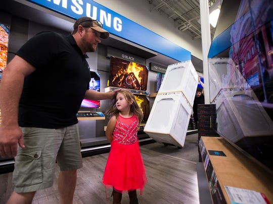 Lance Hetland (left) and his daughter Violet Hetland, 8, look at televisions as a Best Buy employee prepares for Black Friday sales, Tuesday, Nov. 21, 2017, at Best Buy.