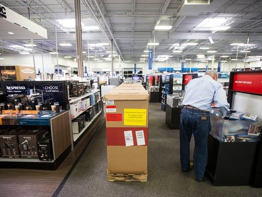 A man raffles through a bin of DVDs at Best Buy, Tuesday,