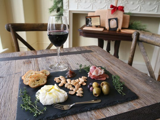 One of the bar bites at the Village Cheese shop that customers can share is a board holding burrata cheese with Marcona almonds, olives and prosciutto di Parma.