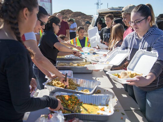 Volunteers prepare food for the homeless at Human Services Campus on Thanksgiving Day 2017 in Phoenix. An empty lot at the Human Services Campus was turned into a makeshift donation center.