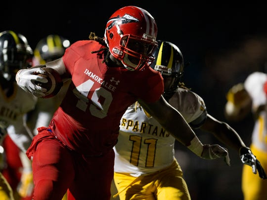 Immokalee's Abraham Alce (49) carries the ball for a touchdown against St. Petersburg-Lakewood during the Class 5A regional final in the first half of action at Immokalee High School Friday, Nov. 24, 2017 in Immokalee, Fla. Immokalee would lead 28-7 at the half.