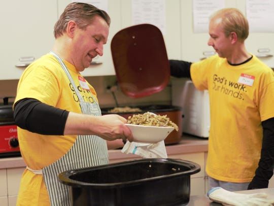 Volunteers Ed Stofcheck and Matt Primmer scoop a batch