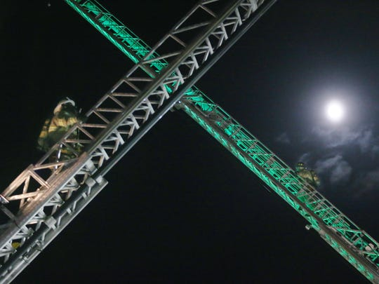 A bright moon looms over the scene as firefighters with Mill Creek Fire Company climb ladders in full gear to maintain readiness.