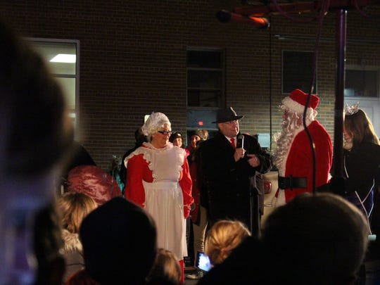 Mrs. Claus, Lexington Mayor Eugene Parkison, Santa Claus and Miss Lexington Grace Riegel, from left, talk to the crowd during Light Up Lexington on Monday, Nov. 27, 2017. It is the 36th year for the annual holiday celebration.