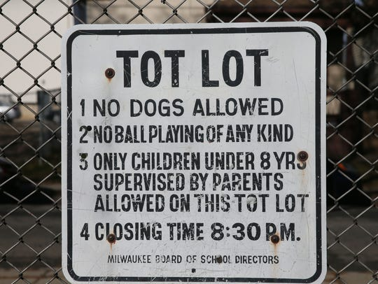 A sign displays rules for using a tot lot at 1354 W. Columbia St. in Milwaukee. Milwaukee Public Schools is targeting the lot for improvements.