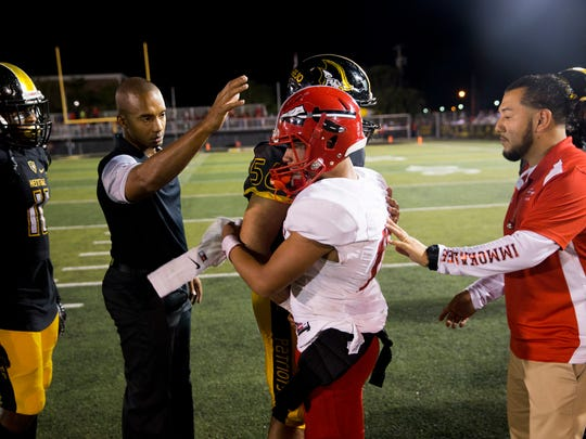 Immokalee quarterback RJ Rosales, center, is consoled