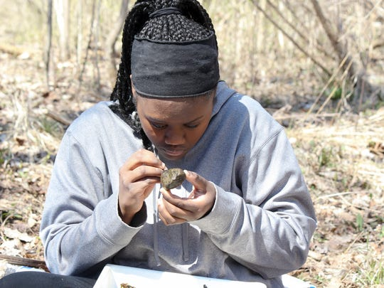 Serena Boegehold, a volunteer with Friends of the Rouge, examines a rock for bugs at the Upper Rouge River in Farmington during the group's Spring Bug Hunt in April 2016.
