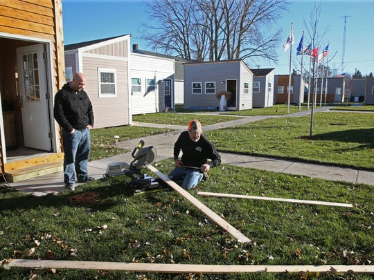 Sean Langley (left), a veteran who is staying in one of the tiny homes, talks with Les Hedrington, a volunteer and member of the board of directors at Veterans Outreach of Wisconsin, as he works on minor updates to the tiny houses.