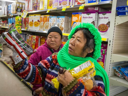 Rupa and Priti Rai look for groceries at the Dollar General Story on 63rd Street in Des Moines on Wednesday, Dec. 6, 2017.