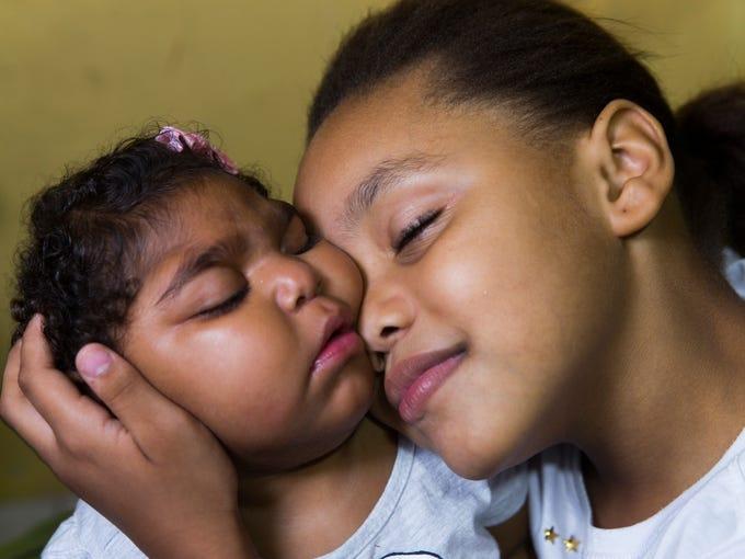 Eduarda Lopes, 9, holds her sister, Valentina Vitoria
