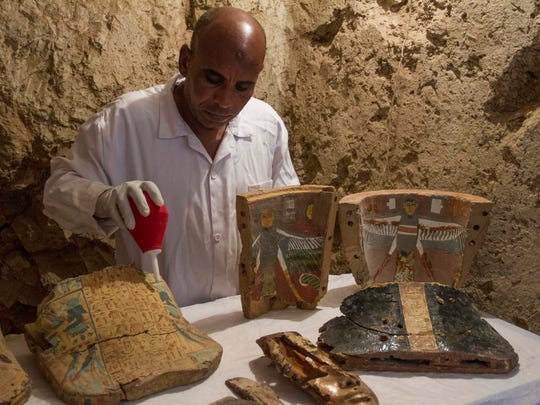 An Egyptian excavation worker restores funeral furniture