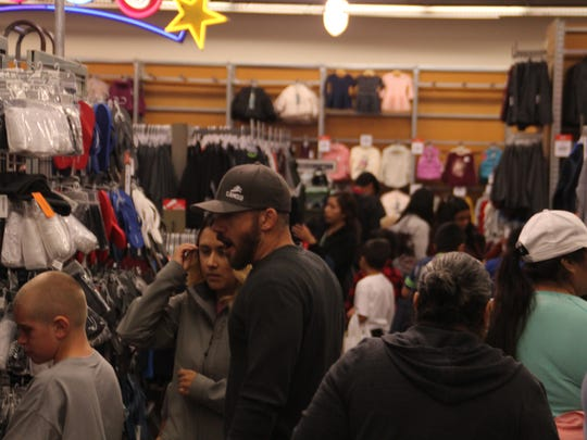 Volunteers shop with kids for clothes at the 69th annual Children's Shopping Tour at Northridge Mall Saturday.