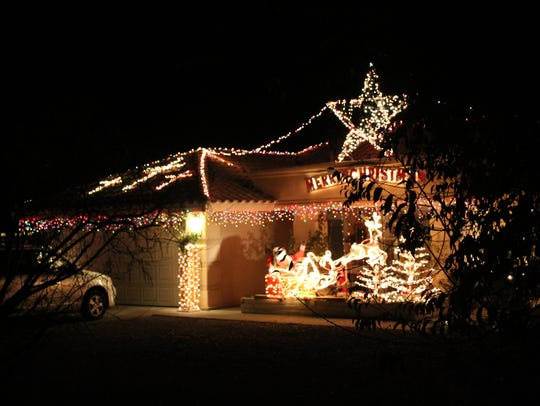 Golden lights and a giant star are featured in the festive display at 5140 Noche Bella Loop.