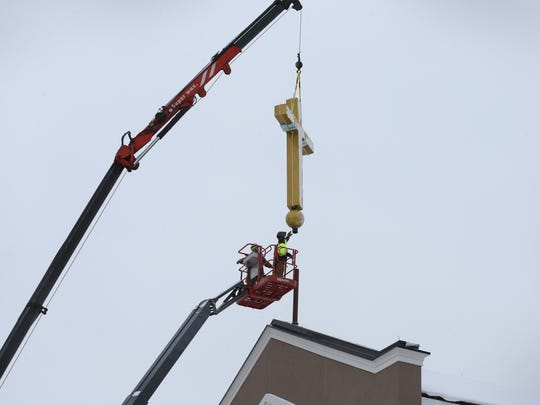 Workers from Kozel Steel install the large cross atop St. Pius Church in Chili Friday, Dec. 15, 2017. The church was badly damaged by a fire on New Year's Day 2015.