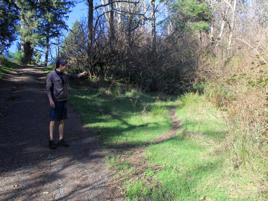 Eric Johnson points to an easement that allows hikers