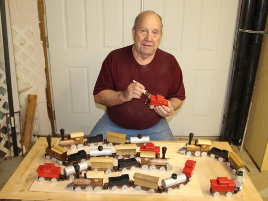 Tellico Village Woodworker Herb West paints toy trains.