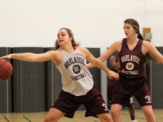 Chesney Gardner, left, chases down an errant pass during a recent practice. The Warlassies' junior forward would pick up her 1,000th career point the following night