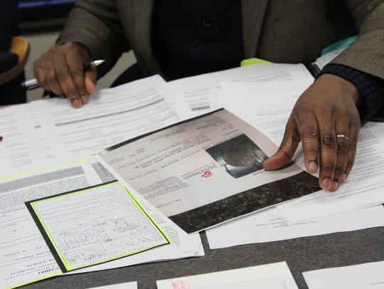Interim Shelter Director Kelvin Samuel holds a replica of a kennel card created by the parish's current software system, Pet Point Professional.