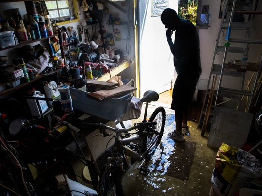 Dave Stroshein inspects the flooding in his shed at
