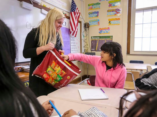 Paola Rios Rosario, right, a Lincoln High School junior, picks out a snack in Nicole Ellis' English language class Dec. 20 in Des Moines. Rosario arrived from Toa Baja, Puerto Rico, in November after Hurricane Maria devastated her hometown.