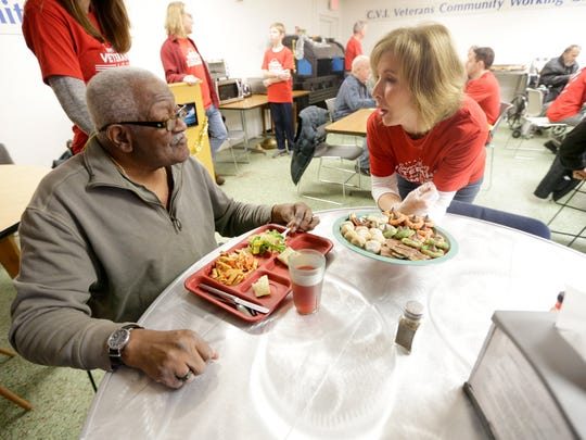 Volunteer Judy Amateis (right) talks with James Bradford, an  Air Force veteran, as Amateis passed around cookies.