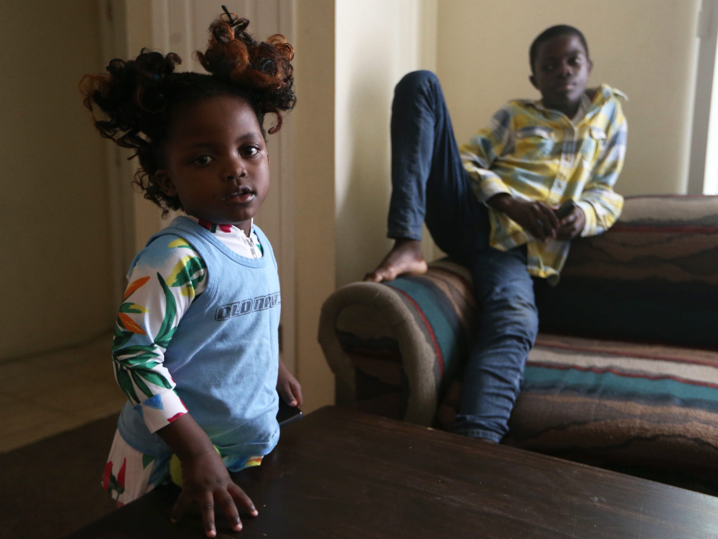 Magi, 4, and James Mambo, 14, in the family's living room in Tallahassee, just a month after they were relocated, receiving refugee status after fleeing the Democratic Republic of the Congo.