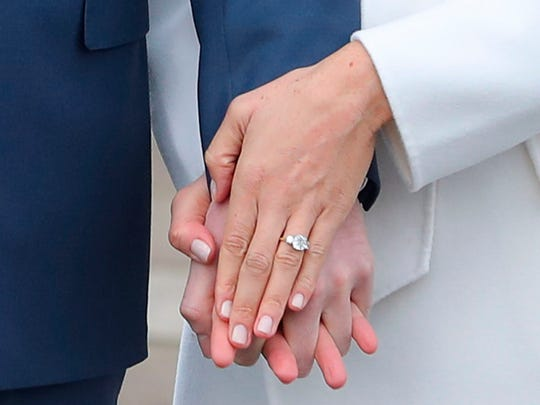 Prince Harry stands with his fiancée, Meghan Markle, in the Sunken Garden at Kensington Palace in London as she shows off her engagement ring following the announcement of their engagement, Nov. 27, 2017.