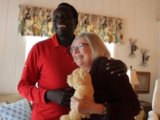 Victor Deng and Patricia Beall share a laugh, holding the stuffed animal she received from the doctor when she was diagnosed with terminal cancer. She sponsored and mentored Deng when he first came to the U.S. 16 years ago as a Sudanese refugee. Since then, she's been like his mother, Deng said.