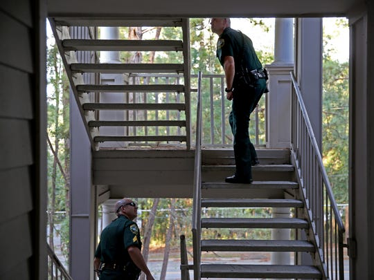 LCSO Sgt. Chris Poole (left) and Deputy John Baas search an apartment complex for a man with outstanding warrants Tuesday, Oct 10.