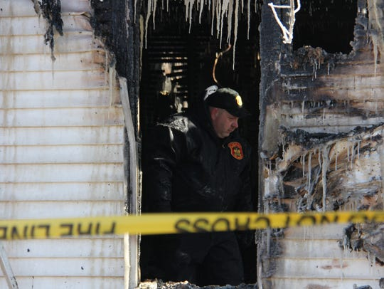 An investigator probes the southwest corner of the gutted home where two people died in a fire New Year's Day in Bolivar.