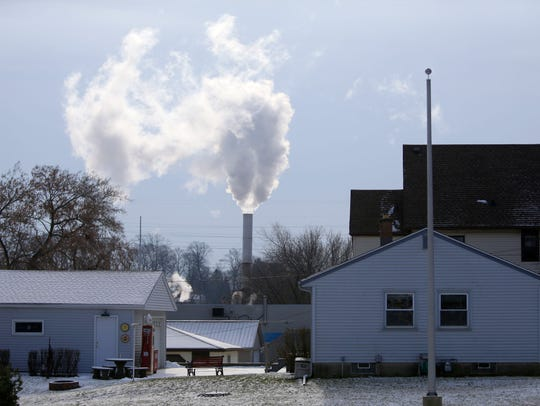 Emissions pour from a stack near neighboring homes