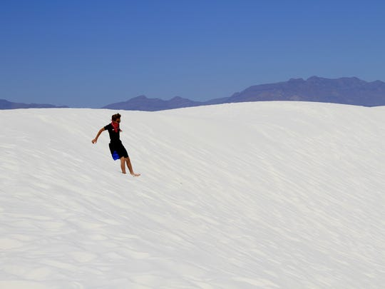 In this May 2016 file photo, a White Sands National Monument visitor slides down a dune at the monument. Dara Parker, spokeswoman for Sen. Martin Heinrich, will be providing information on the White Sands National Park Establishment Act at Thursday's Otero County Commission meeting.