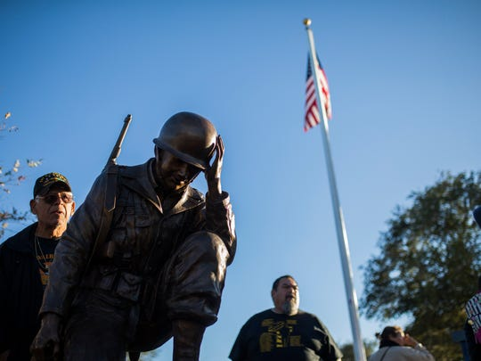 A admires a statue that is part Veterans' Memorial
