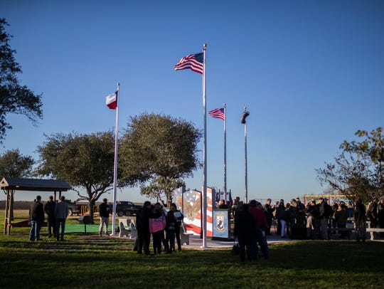 People surround the Veterans' Memorial Wall  after