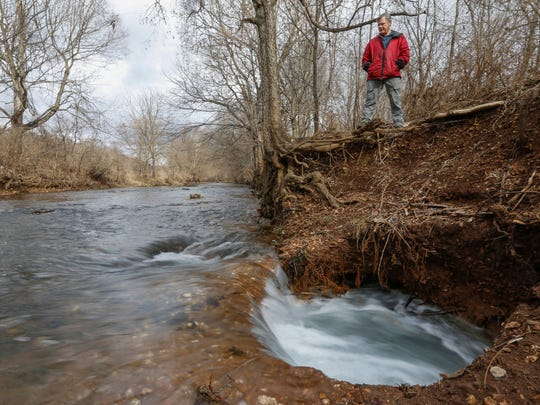 News-Leader outdoors reporter Wes Johnson looks at a new swallow hole that has opened up on Wilson?s Creek near the Wilson's Creek Greenway Trail.