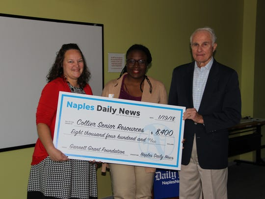 Naples Daily News editor Penny Fisher, left, awards a $8,400 check to Tatiana Fortune and Tom Gleason with the Collier Senior Resources on Jan. 19, 2018.