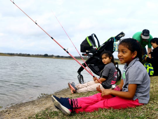 Allyssa Trevino, 5, fishes for rainbow trout with her cousin Ellianna Sanchez, back, during the 23rd Annual Kid Fish event Saturday Jan. 31, 2015 at Lake Corpus Christi State Park in Mathis.