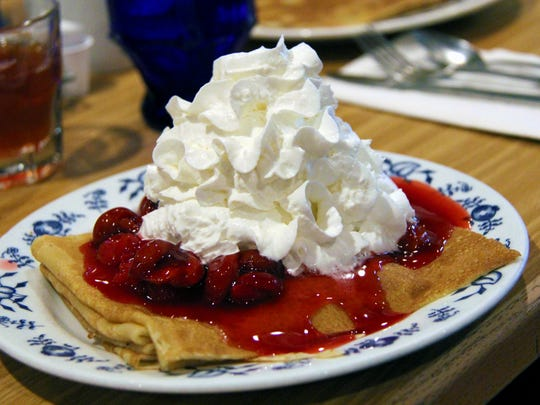 Swedish pancakes at Al Johnson's are topped with Door County sour Montmorency cherries or organic Swedish lingonberries and plenty of whipped cream.
