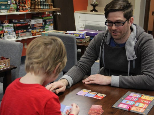 Nathan Perry, co-owner of Ticket to Ride Board Game Cafe, plays Sushi Go! with his son, Eison Perry.