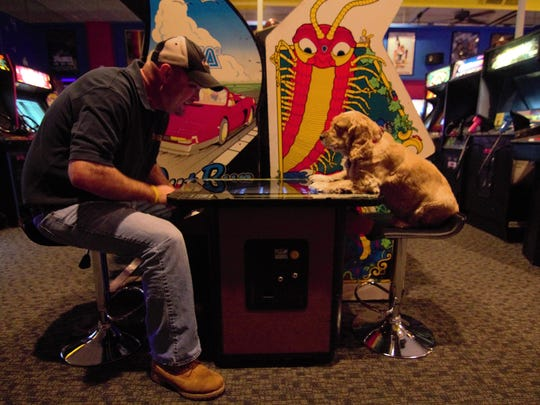 YESTERcades owner Ken Kalada is pictured with his 5-year-old cocker spaniel, Tabitha, playing a cocktail version of Space Invaders.