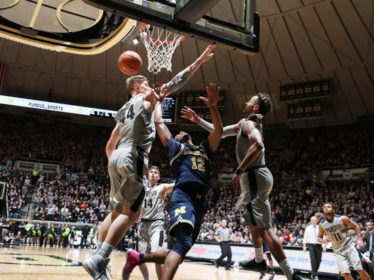 Jan 25, 2018; West Lafayette, IN, USA; Michigan Wolverines forward Muhammad-Ali Abdur-Rahkman (12) takes a shot against Purdue Boilermakers center Isaac Haas (44) and forward Vincent Edwards (12) during the second half at Mackey Arena. Mandatory Credit: Brian Spurlock-USA TODAY Sports