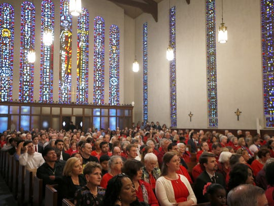 Parishioners listen to a sermon during the annual Red