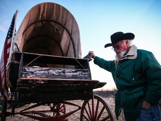 Frank Burkdoll checks his wagon, made around 1900,