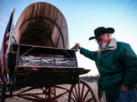 Frank Burkdoll checks his wagon, made around 1900, on the first night of the Santa Fe Trail Ride and Wagon Train Friday, Jan. 26, at U Ranch north of Sterling City.