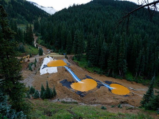 FILE--In this Aug. 12, 2015, file photo, mine wastewater flows through a series of retention ponds built to contain and filter out heavy metals and chemicals from the Gold King Mine chemical accident in the spillway about 1/4 mile downstream from the mine, outside Silverton, Colo. Crumbling mine tunnels awash with polluted waters perforate the Colorado mountains, and scientists may one day send robots creeping through the pitch-black passages to study the mysterious currents that sometimes burst to the surface with devastating effects. (AP Photo/Brennan Linsley, file)