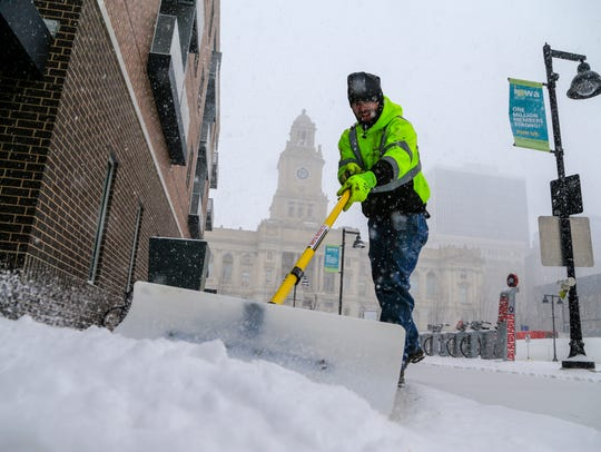 Adam Green shovels snow from the sidewalk outside the