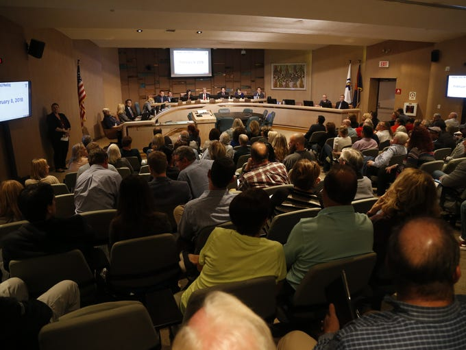 People gather at the City Council meeting at the Municipal